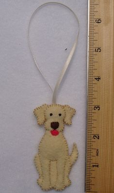 This little pup would love to hang on your Christmas tree, or hang from your car mirror, or be a special present for someone special. He is entirely sewn by hand with tiny little stitches. He is made of acrylic felt, embroidery thread, and polyfil. There is a picture of him by a ruler so that you can get an idea of his size and the size of the cream color satin ribbon attached to him. There is also a close-up of his front and a picture of his back. The pictures that you see here are of the…