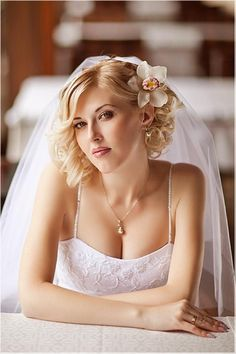 Chin length curly blonde with a side part and side swept bangs wedding hairstyle with a flower hair accessory