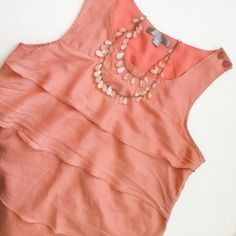 "Silk Tiered Blouse✨ 100% silk • light pinkish-orange color -- I'd describe it as ""Salmon"", it's absolutely gorgeous in person! • tiered, flattering style • hidden side zipper • 2 button detail on top of shoulder • there are the tiniest dot marks on the front (see photo 3) that are barely noticeable but thought it was worth mentioning • this sleeveless blouse would look flawless on sunkissed tan skin, get it in time for summer!☀️ Tops Blouses"