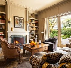 Painted wood-paneled walls, a fireplace, and plush furnishings create a cozy library. - Traditional Home ® / Photo: John Granen / Design: Mary Silk