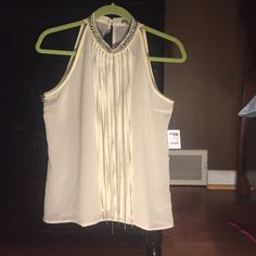 Charlotte Russe top Sleeveless cream colored halter; high neck with beading. Long fringe and chain embellishment attached to neckline. Fun top. States large, fits a medium. Polyester. Length 26 inches. Charlotte Russe Tops