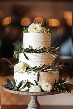 white wedding cake adorned with olive leaves