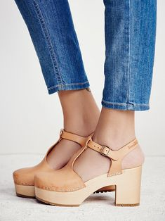 Lotta Clog   Leather clogs featuring adjustable ankle straps for an easy, comfortable fit. Wooden heels provide a vintage-inspired aesthetic. Textured rubber soles.