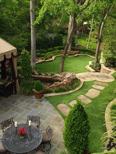 #Landscaping #LandscapingIdeas #Backyard  #tieredgarden / This landscape design takes advantage of the hilly backyard. At the top of the hill, near the house, there are two patio seating areas for eating and/or casual conversation. A stone path leads you down to the next level of the lawn, an open grassy area, surrounded by carefully chosen plants. Please note the small pond by the patio, which adds even more interest. Source: https://homebnc.com/best-backyard-landscaping-ideas/