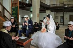 A Crimean Tatar couple listen to a Muslim cleric during a wedding at the Great Khan mosque [Denis Sinyakov/Al Jazeera]