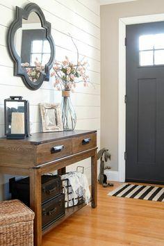 recibidores originales, decoración con aparador de madera, espejo en forma irregular, flores secos rosados, tapete rayado, pared de tarima blanca