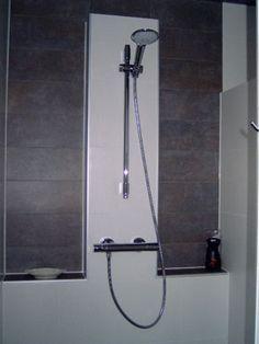 Een badkamer met warme kopertinten en een nis voor o.a. de shampoo- en doucheflessen. Gerealiseerd door Sanidrome Ester Oom in Goes.