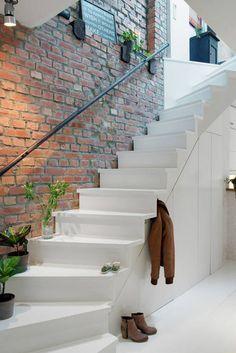 Gładkie, lśniące, starannie wykończone schody z pomalowanej na biało płyty kontrastują ze ścianą z surowej cegły. Miejsce pod schodami sprytnie wykorzystano na zabudowany schowek – praktyczny, a mało widoczny.