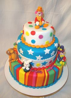 3 tier circus theme cake with clowns and monkey and rabbit in a hat.
