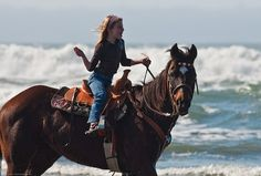 Little girl equestrian riding her horse in the water on Morro Strand State Beach