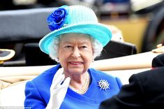 The Queen, wearing a rather fetching sky blue hat topped with a royal blue rose which matched her dress