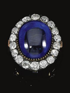 THE PROPERTY OF H. S. H. PRINCE CARLO DELLA TORRE E TASSO - JEWELS FORMERLY FROM THE COLLECTIONS OF PRINCESS MARIE BONAPARTE AND PRINCESS EUGENIE OF GREECE AND DENMARK AND THENCE BY DIRECT DESCENT SAPPHIRE AND DIAMOND BROOCH/CLASP, MID 19TH CENTURY Set with a cabochon sapphire within a border of eighteen cushion-shaped diamonds, mounted in silver and gold, French assay marks and partially legible maker's marks.