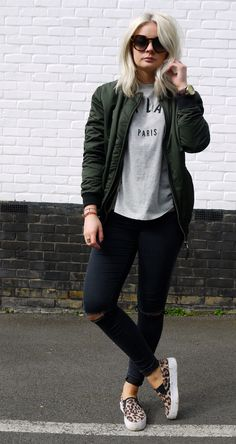 Cool street style: khaki bomber jacket, leopard print vans, black distressed jeans, basic printed tee and boyfriend watch.  Sweet.