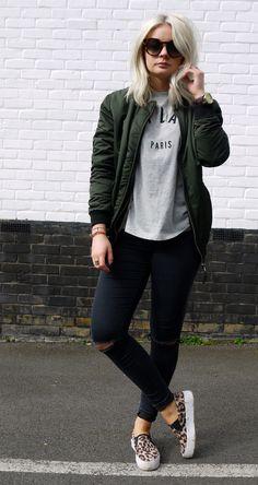 Cool street style: khaki bomber jacket, leopard print vans, black distressed jeans, basic printed tee and boyfriend watch.  Sweet.