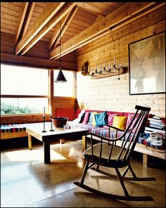 Norwegian Wood-Jürgen Kiehl upgraded his 1970s Norwegian vacation home from the original structure he built as a young architect. Here, built-in benches function both as seating and as spare beds in the living room. His wife, Kari Holm, says the striped, hand-woven fabric she found in Greece is indestructible, and the cork flooring throughout the house has gone 40 years without needing replacing. Photo by: Pia Ulin