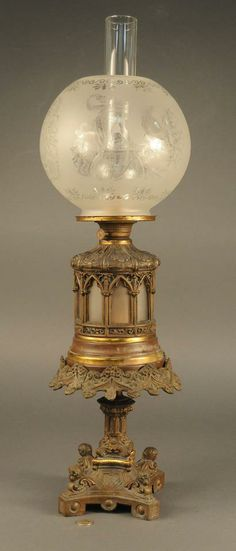 Rare Victorian oil lamp, etched glass shade with classical scenes. Base has four cherubs perched on each corner foot. Oil chamber has a frosted glass insert visible through Gothic cutout panes.