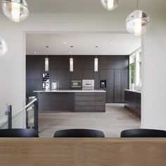 Round pendant lighting in the dining room contrasted with the rectangular lights over the kitchen island.