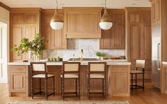 Lit by brass pendants, a honey stained oak kitchen island is accented with cabinets adorned with brass pulls topped with thick white marble fitted with a sink and polished brass gooseneck faucet lined with wood  barstools upholstered in cream fabric.