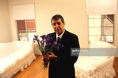 Canadian singer/songwriter Leonard Cohen stands in a sparsely decorated room in his West Hollywood home, Hollywood, California, 1992. Dressed in a dark suit and tie, he holds a bouquet of purple flowers. (Photo By Paul Harris/Getty Images)