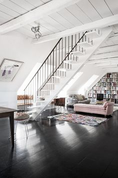 black floors, white sealing, pink chaise and books