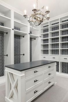 Well appointed white and gray walk-in closet features A Visual Comfort Armillary 6 Light Chandelier hung above a white center island fitted with an x-trim and contrasted with a black countertop and matte black pulls. Master Closet Design, Walk In Closet Design, Master Bedroom Closet, Closet Designs, White Bedroom, Master Closet Layout, Bedroom Closet Storage, Dressing Room Closet, Bedroom Closets