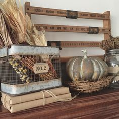 Rustic fall decor for a shelf or mantel, featuring autumn indian corn cobs with dried corn husks in a metal wire basket, and ceramic pumpkin sculpture sitting in a nest. Country cottage style decorating.
