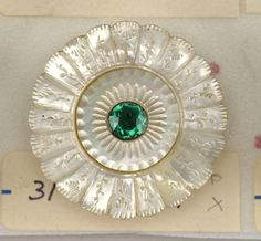18th century mother of pearl button with green glass jewel.
