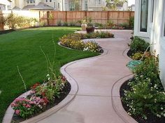 Nice back yard landscaping with curved walk leading to a patio area.