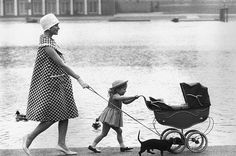 Pregnant Mother, daughter, dachshund and doll stroll along in Hyde Park, London, 1959