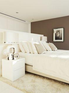 un lit blanc et élégant et un mur marron dans la chambre à coucher