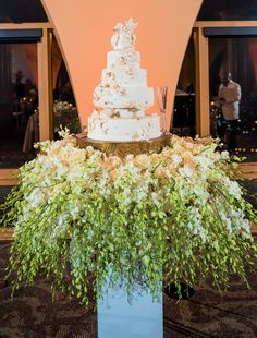 Stunning white and gold cake with cake table covered in white and green floral on pedestal. New Year's Eve Wedding   Floral and Decor by Southern Event Planners  Photo by SkyTouch_E_Photos