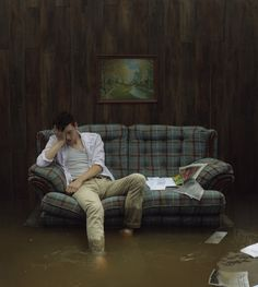 Kyle Thompson - Ghost Town (2014-). Flooded living room. Guy on a couch.