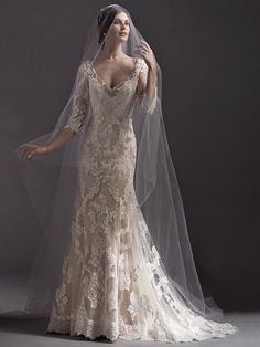 Sottero and Midgley - ANNORA, Stunning lace appliqués trail the skirt of this slim A-line wedding dress, complete with illusion lace three-quarter sleeves and V-neckline, adorned with Swarovski crystals. Finished with pearl button over zipper closure.