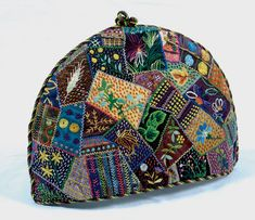 A velvet and silk multi-coloured crazy pieced patchwork tea cozy with amazing floral embroidery. Maker: Unknown - Date: 1900 - 1925
