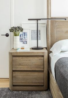 Classic, neutral inspired bedroom with a wood nightstand, layered art, and a reading lamp