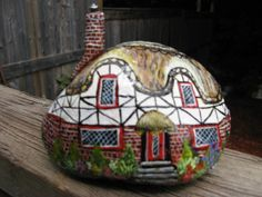 Tudor style English cottage. Black and white top with red brick on bottom part: surrounded by colourful garden