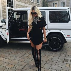 Wheretoget - Black ripped dress, black knee-high lace-up boots, black sunglasses and oversized silver necklace