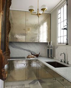 The cabinetry in the kitchen is clad in hammered silver, and the countertops and floor are marble; the brass-and- opaline light fixture is by Stilnovo, and the sink is by Franke.