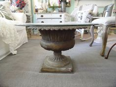 Garden urn with glass becomes a beautiful coffee table.  Love this idea, can put decorative colored or natural wicker orbs inside, or anything you would like to showcase, even sand and seashells...