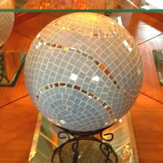 This was once a bowling ball, now it is a work of art. I used over 1500 individually cut pieces of white glass & mirror bits. Check out my other custom, one of a kind mosaics at http:www.mosaicillusions.etsy.com
