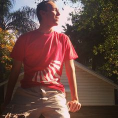Greyson posted up on a #fence #red #white #design #nature #sunlight #sunny #realdope #clothing #modeling