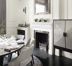 A custom designed drinks cabinet by Knowles & Christou sits adjacent to a grand period fireplace with contrast marble insets, of which there are several in the home. The mirror, sourced from Louise Bradely, provides understated elegance.