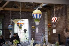 DIY Hot Air Balloon floating centerpieces! Made by painting playground balls and having plant containers as the baskets. These would be cool just hanging from a tree in a garden.