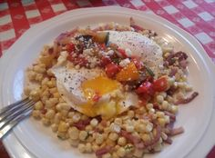 Over-easy eggs served on saute of corn & country ham with thyme finished with ratatouille and feta.