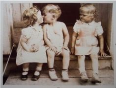 Two little girls and a boy in sitting on front steps, the boy is kissing one. The other needs some dating advice for women.