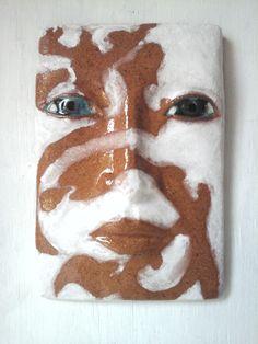 White slip over terracotta buff raku trachyte clay body.