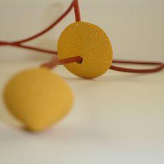 Collar de cuero color naranja con piezas móviles en arcilla polimérica rugosa de color mostaza. La medida de esta pieza puede regularse consiguiendo un efecto gargantilla o bien manteniendo su longitud original a la medida del pecho.