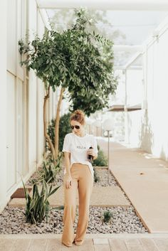Renewed Favorites | Clothes & Quotes. White graphic t-shirt+camel wide-leg pants+black ankle strap heeled sandals+black clutch+sunglasses. Summer Dressy Casual Outfit 2017