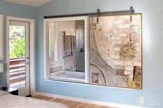 Art sliding window allows soaker to watch TV from the tub.