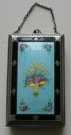 Art Deco Enameled Sterling Minaudiere This lovely Art Deco minaudiere features an enameled flower basket on a light aqua blue background with a black border.  The inside include a mirror, a lipstick holder and a place for a puff and rouge.